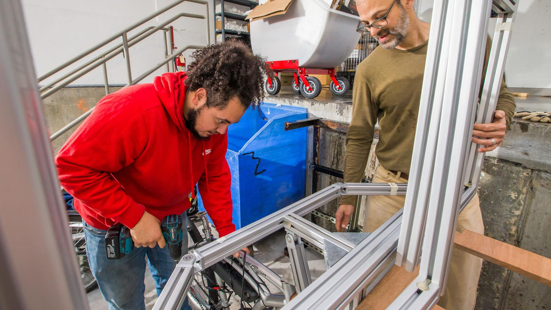 Sebastian Silva '20 and Associate Professor Jonathan Harris working on their solar-powered delivery bike.